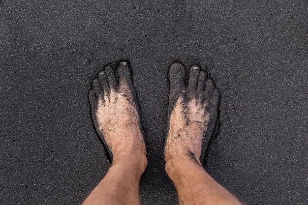 Ein mann, der barfuß auf vulkanischem schwarzem sand am strand von teneriffa steht. zwei fuß vom sand bedeckt.
