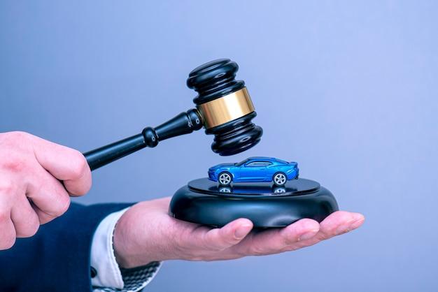 Ein mann, der blaues auto auf hölzernem richterhammer, konzeptbild über autokreditschuld oder scheidung hält.