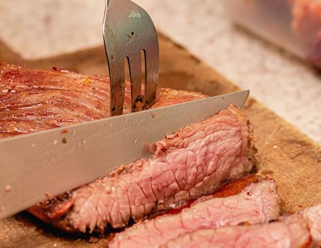 Ein mann, der brasilianisches grillfleisch mit einem messer auf den punkt schneidet