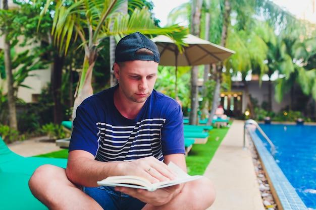 Ein mann, der buch neben schwimmbad im garten liest.