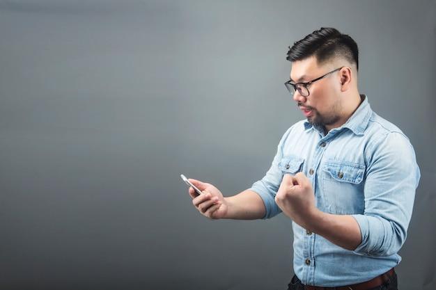 Ein mann, der das telefon mit erstaunen auf einem grauen hintergrund betrachtet