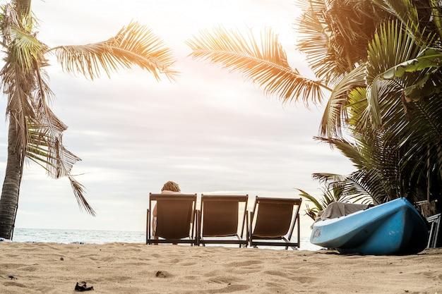 Ein mann, der die atemberaubenden ansichten des tropischen sandigen strandes mit grünen kokosnusspalmen und schönem sauberem seeozean genießt