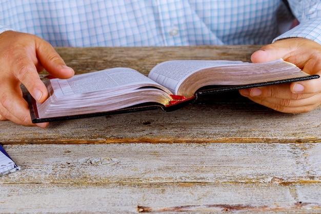 Ein mann, der die heilige bibel nahe hände liest