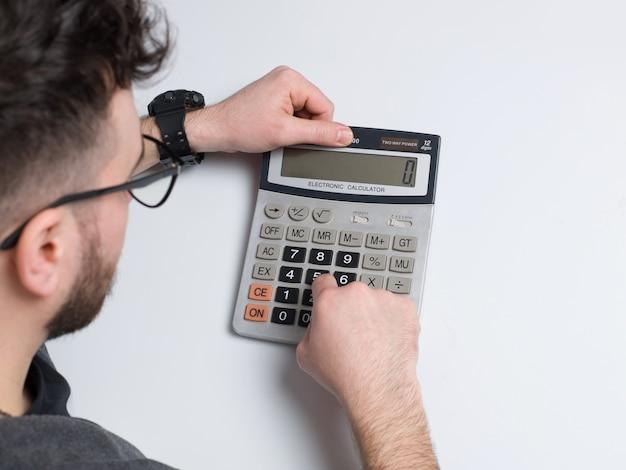 Ein mann der draufsicht, der taschenrechner auf dem weißen schreibtisch benutzt