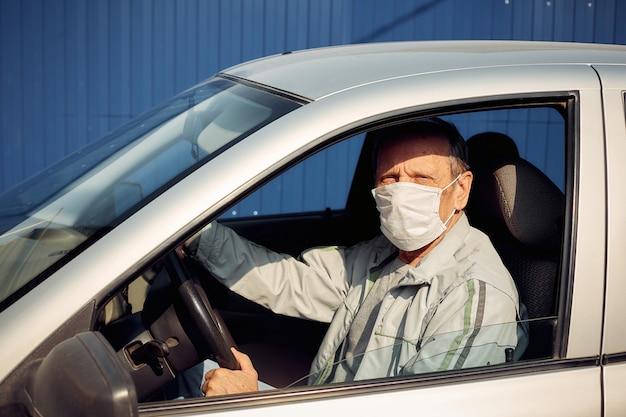 Ein mann, der ein auto fährt, setzt während einer epidemie eine medizinische maske auf, ein taxifahrer eine maske, um sich vor dem virus zu schützen
