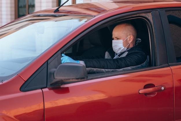 Ein mann, der ein auto in einer schützenden medizinischen maske und handschuhen fährt. sicheres fahren in einem taxi während einer pandemie-coronavirus. schützen sie fahrer und passagiere
