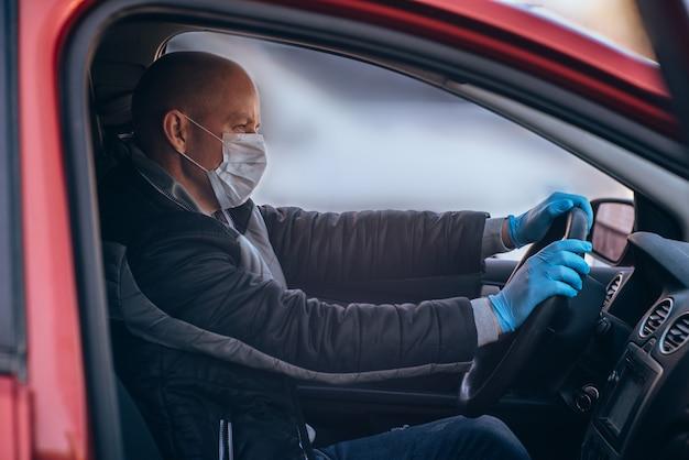 Ein mann, der ein auto in einer schützenden medizinischen maske und handschuhen fährt. sicheres fahren in einem taxi während einer pandemie-coronavirus.