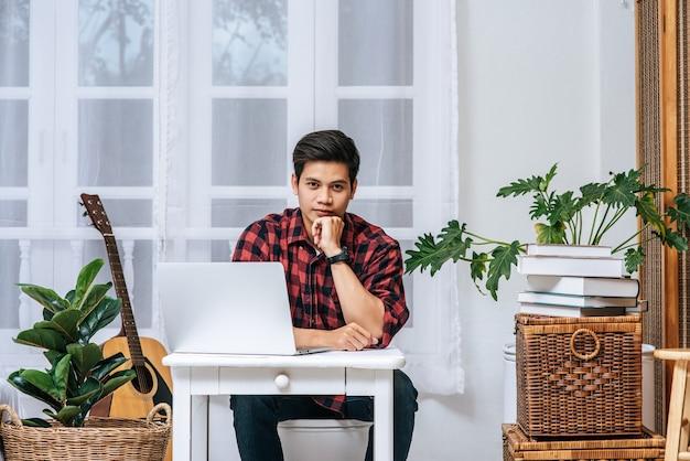 Ein mann, der ein gestreiftes hemd trägt, benutzt einen laptop, um zu arbeiten.