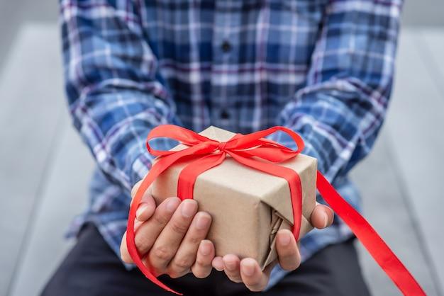 Ein mann, der ein handwerksgeschenk gebunden mit rotem band hält.