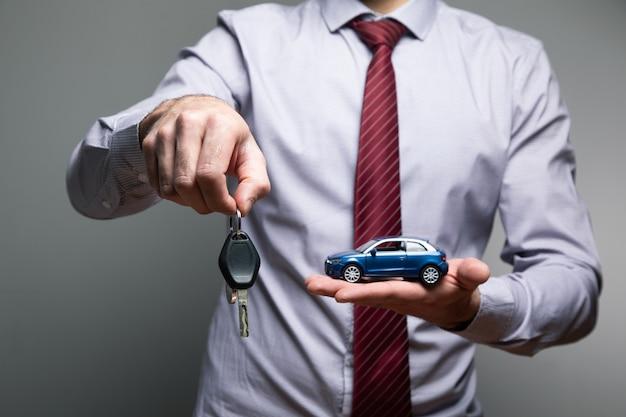 Ein mann, der ein spielzeugauto und schlüssel in seinen händen hält.