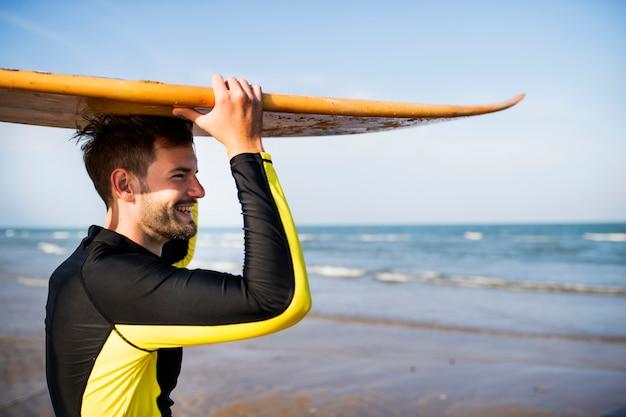Ein mann, der ein surfbrett trägt