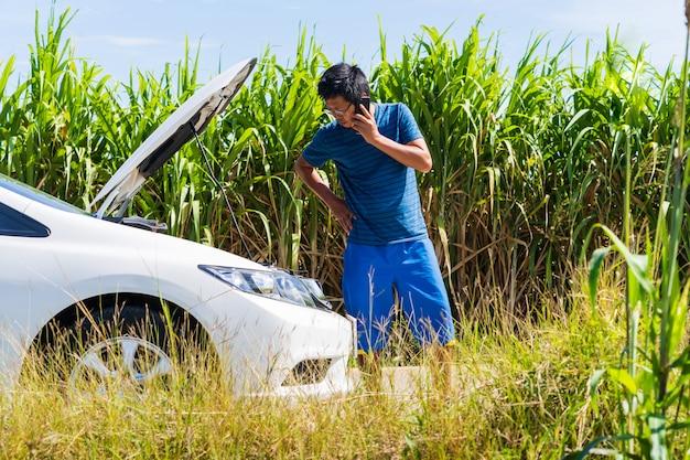 Ein mann, der ein telefon verwendet, während er ein problemauto auf der straße hat