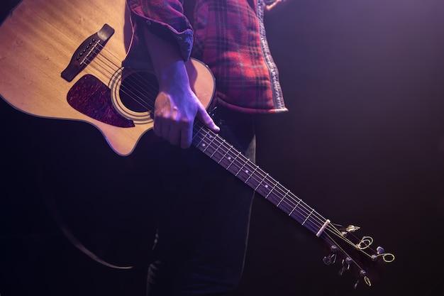 Ein mann, der eine akustikgitarre in seinen händen hält, kopiert raum.