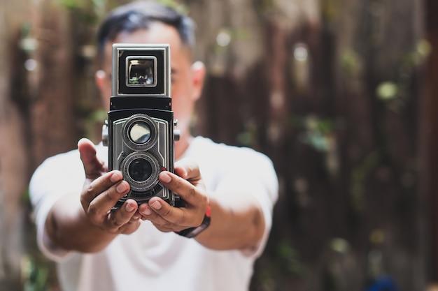 Ein mann, der eine analoge vintage-kamera zeigt