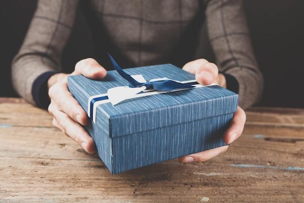 Ein mann, der eine geschenkbox hält