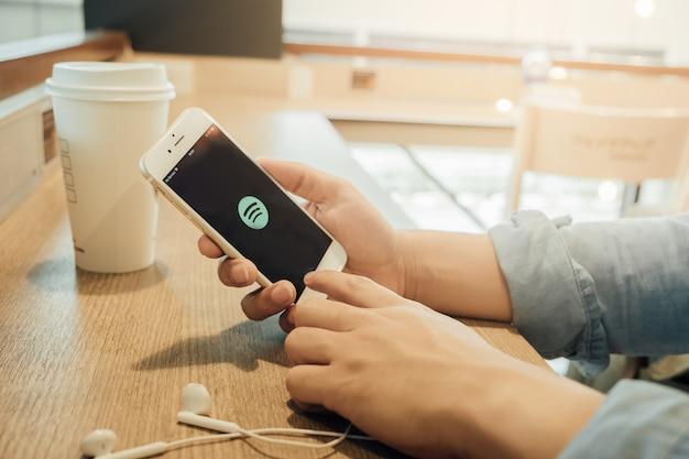 Ein mann, der eine iphone 6 öffnende spotify anwendung hält