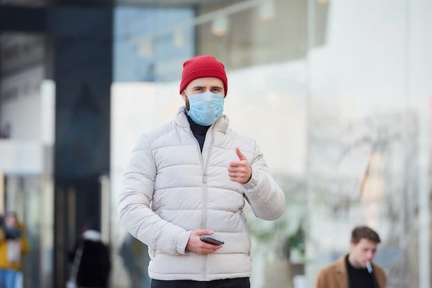 Ein mann, der eine medizinische gesichtsmaske trägt, um das verbreitete coronavirus (covid-19) zu vermeiden.