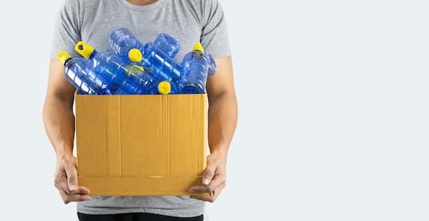 Ein mann, der eine schachtel mit einer plastikflasche trägt, die recycelt werden soll
