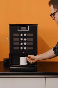 Ein mann, der eine tasse in der nähe einer schwarzen kaffeemaschine hält