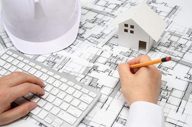Ein mann, der einen bleistift in der hand hält und architekturzeichnungen malt