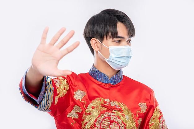 Ein mann, der einen cheongsam und eine maske trägt, zeigt, dass menschen, die keine masken tragen, während des neuen mondjahres nicht einkaufen können.