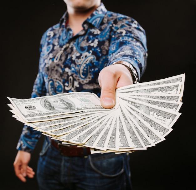 Ein mann, der einen fan von dollarbanknoten hält.