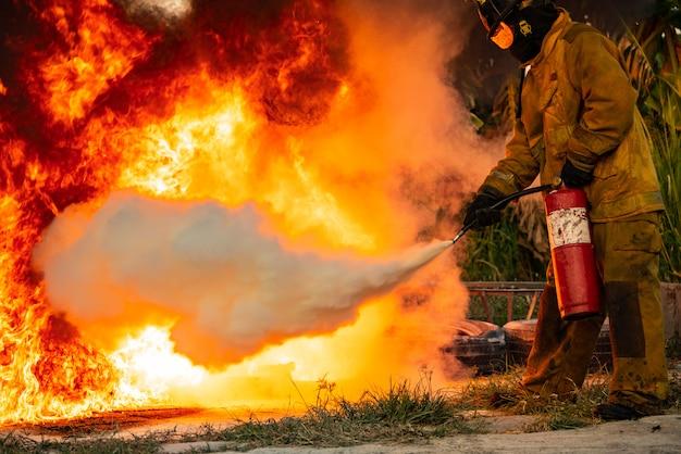 Ein mann, der einen kohlendioxid-feuerlöscher benutzt, um ein feuer zu bekämpfen.