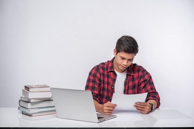 Ein mann, der einen laptop im büro benutzt und eine dokumentenanalyse durchführt.