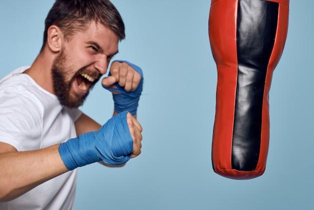 Ein mann, der einen schlag auf einen boxsack in einem weißen t-shirt auf einem blauen hintergrund übt