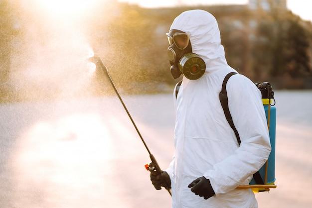 Ein mann, der einen speziellen desinfektionsschutzanzug trägt, sprüht sterilisator auf dem leeren öffentlichen platz im morgengrauen in der stadt der quarantäne. covid 19. reinigungskonzept.