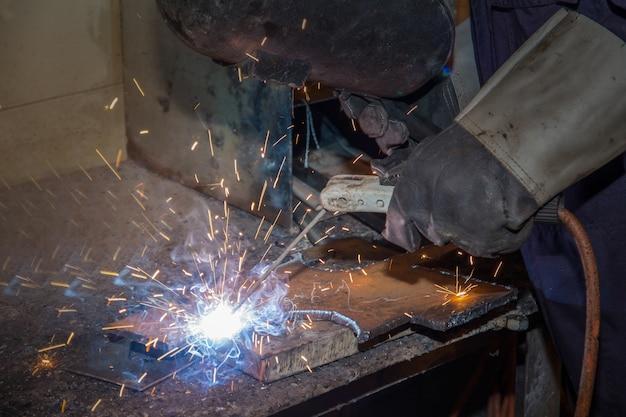 Ein mann, der fabrikschweißer, schneiden, reibend, bohrend arbeitet