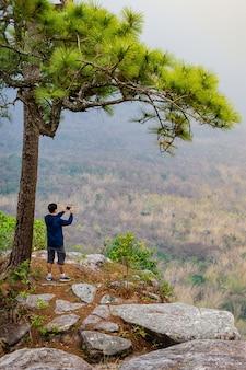 Ein mann, der foto am standpunkt auf rand eines klippennaturhintergrundes macht