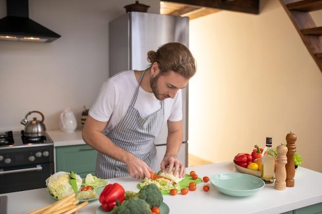 Ein mann, der gemüse für einen leichten salat schneidet