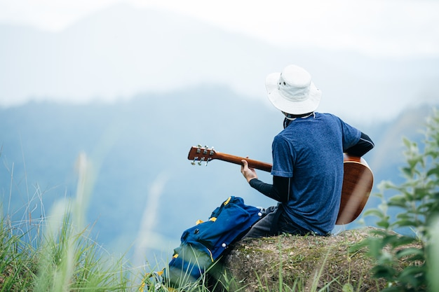 Ein mann, der glücklich sitzt und allein im wald gitarre spielt.