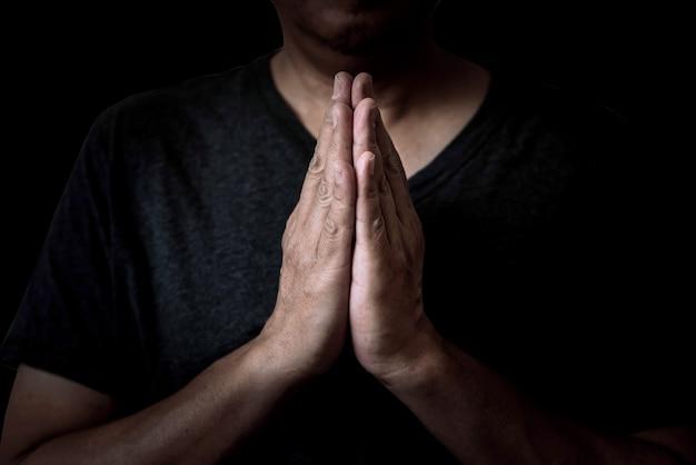 Ein mann, der hände betet, respektiert heilige dinge. er glaubt an gott. auf schwarzem hintergrund