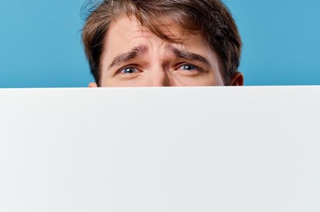 Ein mann, der hinter einem banner hervorschaut, das für copy space-nahaufnahmen wirbt