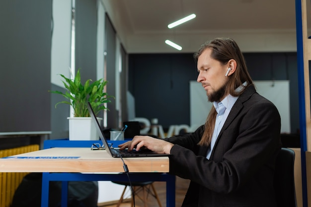 Ein mann, der im büro an einem laptop arbeitet