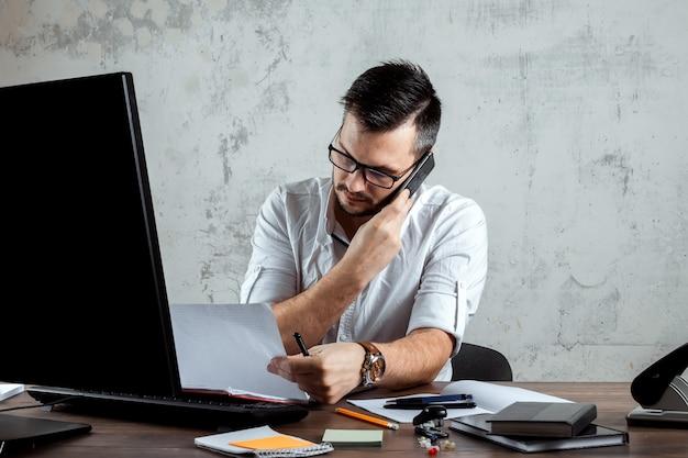 Ein mann, der im büro an einem tisch sitzt und telefoniert, entscheidet über eine wichtige frage. das konzept der büroarbeit, ein startup. kopieren sie platz.
