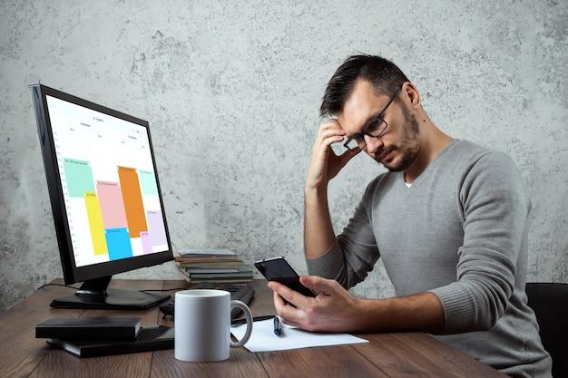 Ein mann, der im büro an einem tisch sitzt und telefoniert, entscheidet über eine wichtige frage.