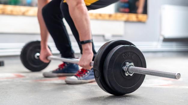 Ein mann, der im fitnessstudio eine langhantel auf dem boden hält