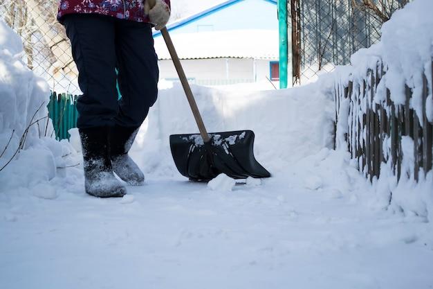 Ein mann, der im schnee stehtdas mädchen putzt den schnee mit einer pfote