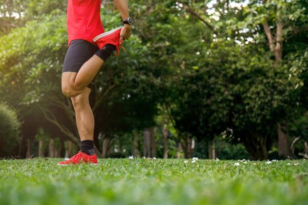 Ein mann, der in den park vor dem laufen am morgen ausdehnt.