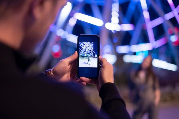 Ein mann, der in der nachtstraße ein foto von einer freundin macht, die ein telefon benutzt Premium Fotos