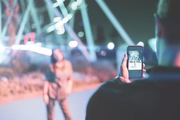 Ein mann, der in der nachtstraße ein foto von einer freundin macht, die ein telefon benutzt