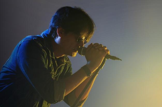 Ein mann, der in ein mikrofon unter scheinwerfer mit rauche auf einem stadium singt