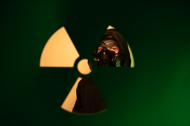 Ein mann, der in einem dunkelgrünen kapuzenpulli mit einer kapuze auf seinem kopf mit einer gasmaske auf seinem gesicht hinter einem unscharfen hintergrund des strahlungsgefahrenkonzepts steht