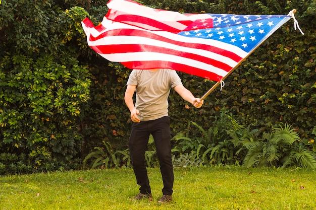 Ein mann, der in wellenartig bewegender armenischer flagge des parks steht