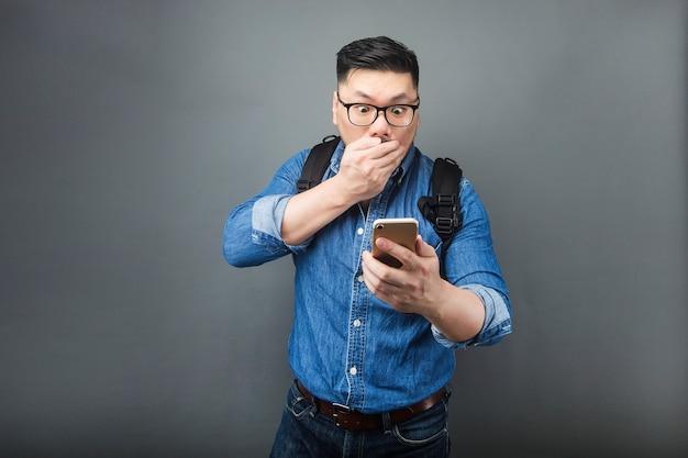 Ein mann, der mit erstaunen das telefon betrachtet