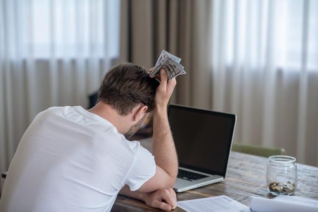 Ein mann, der mit geld in der hand sitzt und verärgert aussieht
