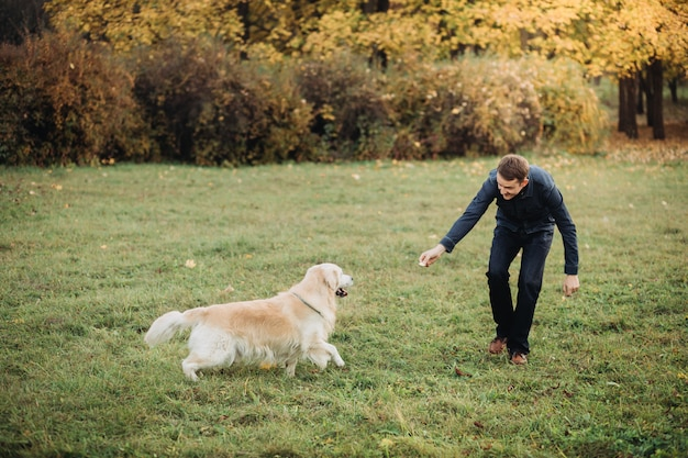 Ein mann, der mit seinem goldenen apportierhund in einem schönen herbstpark spielt